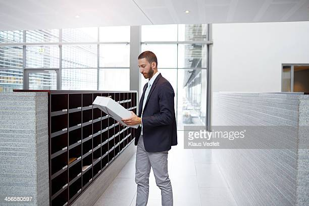 Businessman getting package from dovecote