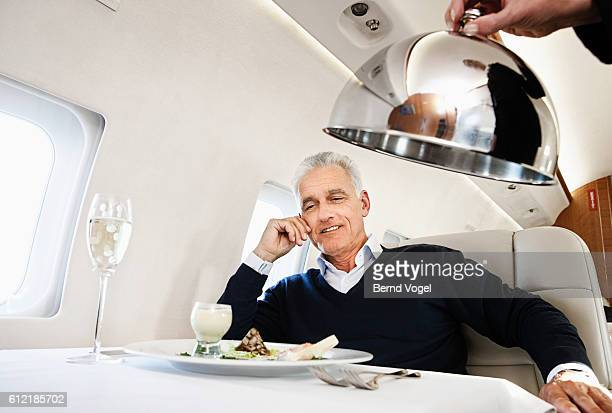 Businessman getting served on an airplane
