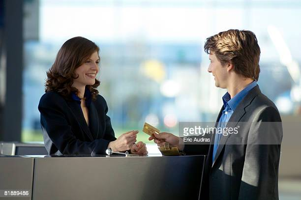 businessman giving a credit card to a hotel receptionist - exchanging stock pictures, royalty-free photos & images