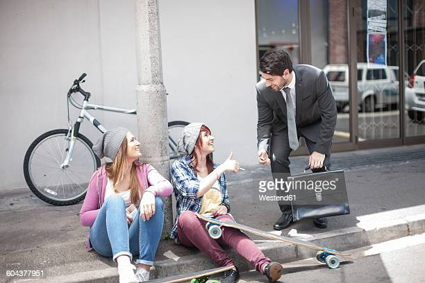 Businessman giving a lighter to two female friends on city street