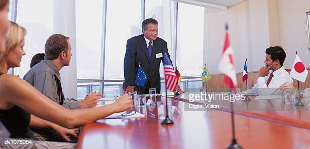 businessman giving a presentation in a conference room to other business executives - 国際連合 ストックフォトと画像