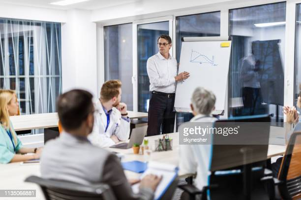 businessman giving a presentation to doctors in the office. - administrator stock pictures, royalty-free photos & images