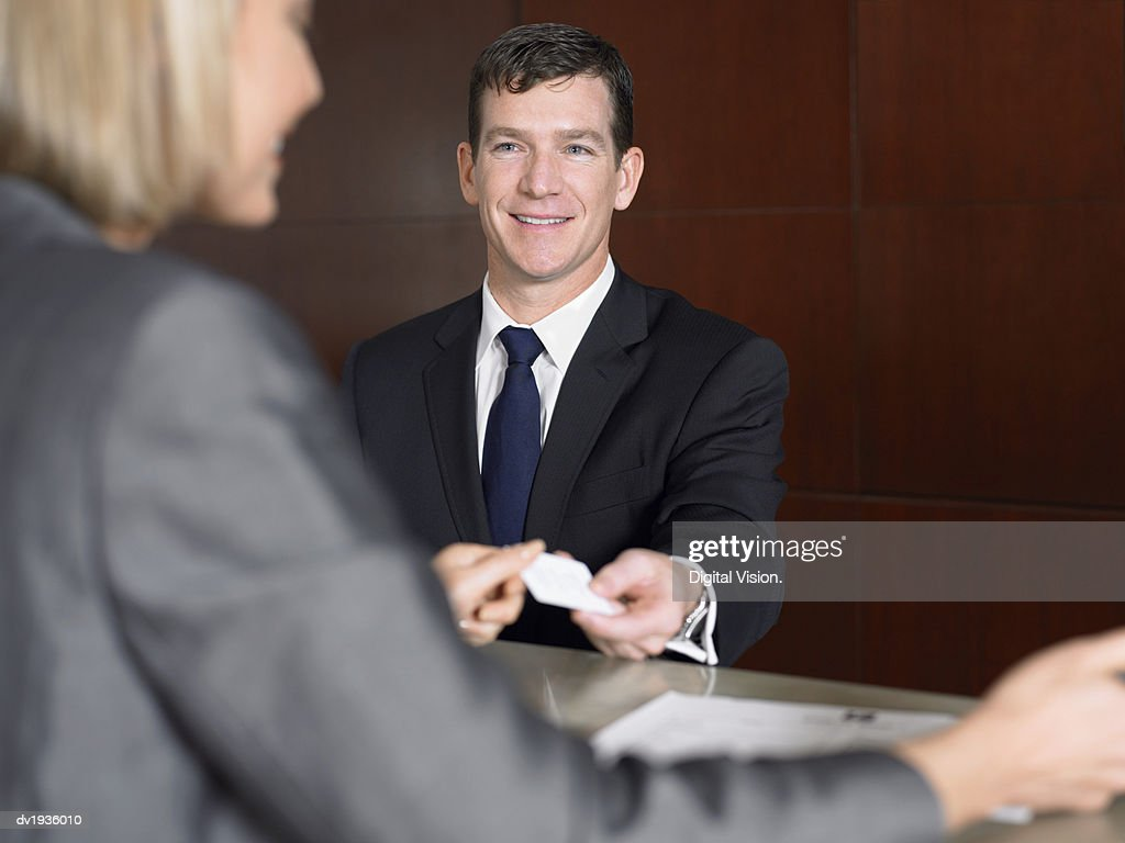 Businessman Giving a Receptionist His Business Card : Stock Photo