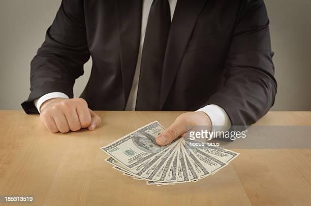 Businessman giving a stuck of money