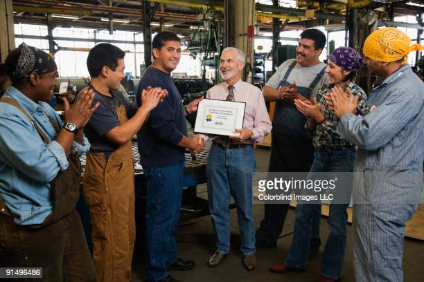 Businessman giving award to warehouse worker