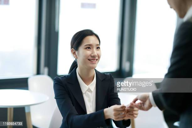 businessman giving business card to businesswoman - 名刺 ストックフォトと画像