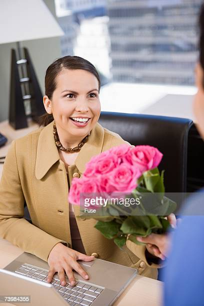 Businessman giving businesswoman roses