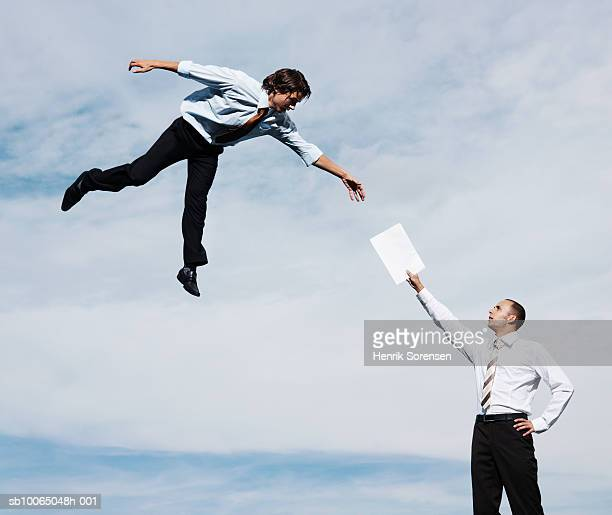 Businessman giving letter to man flying in mid-air