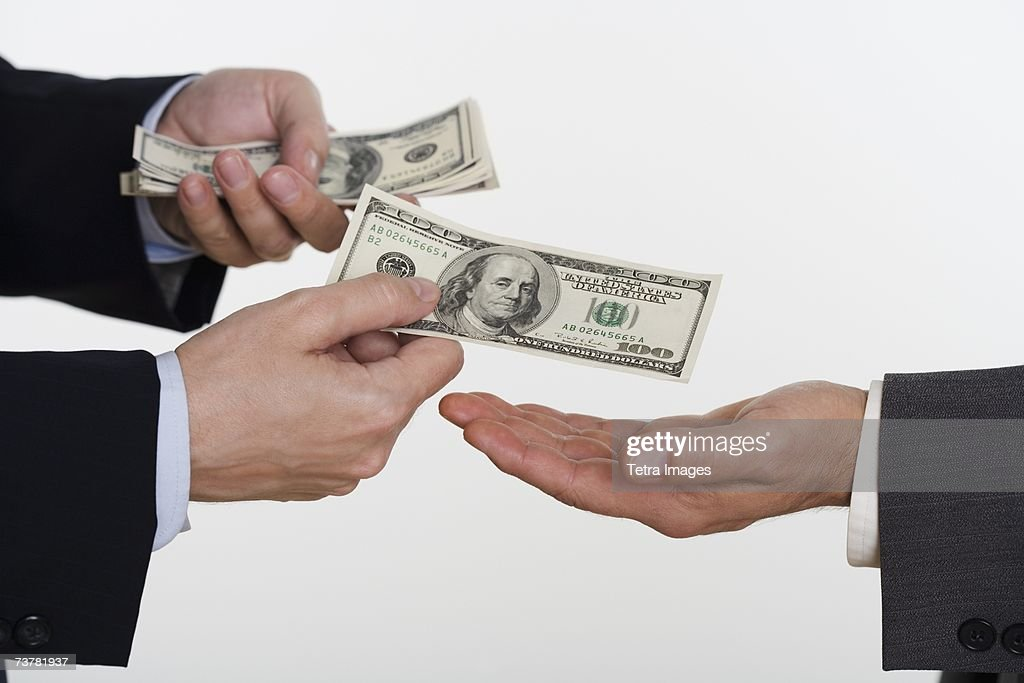 Businessman giving money to a man : Stock Photo