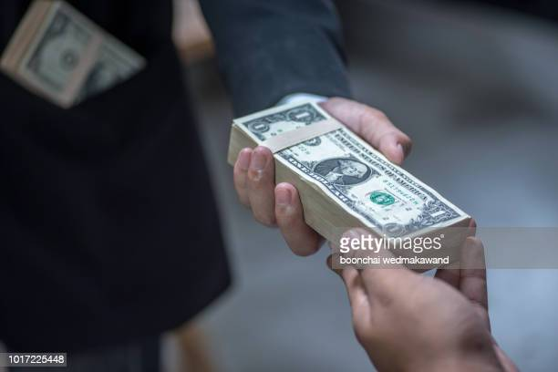 businessman giving money to his partner - payment, loan and bribery concept - money politics stock pictures, royalty-free photos & images