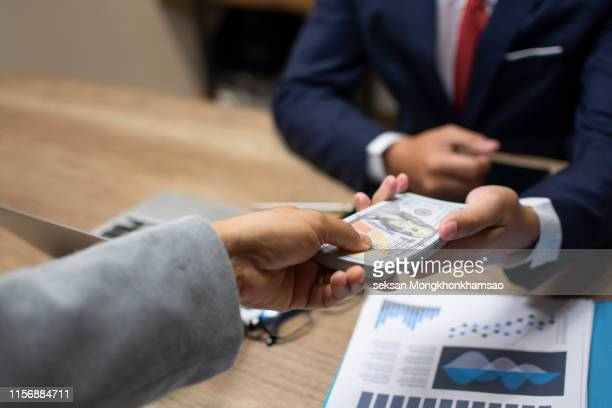 businessman giving money to his partner - payment, loan and bribery concept - wages stock pictures, royalty-free photos & images