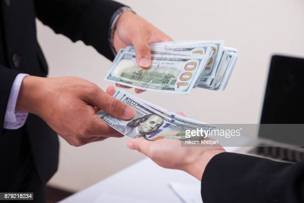 Businessman giving money to his partner while making contract - bribery and corruption concepts