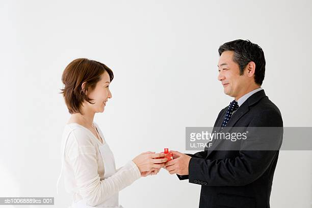 Businessman giving present to woman, studio shot