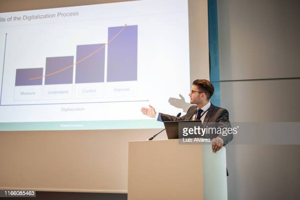 businessman giving presentation at auditorium - one mid adult man only stock pictures, royalty-free photos & images