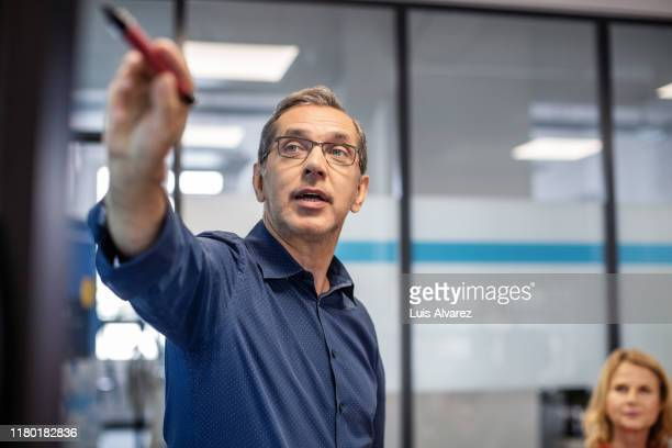 businessman giving presentation in office - tonen stockfoto's en -beelden