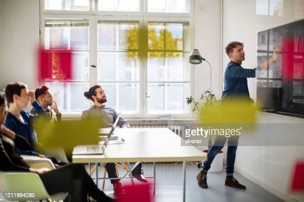 businessman giving presentation inside boardroom - envolvimento dos funcionários imagens e fotografias de stock