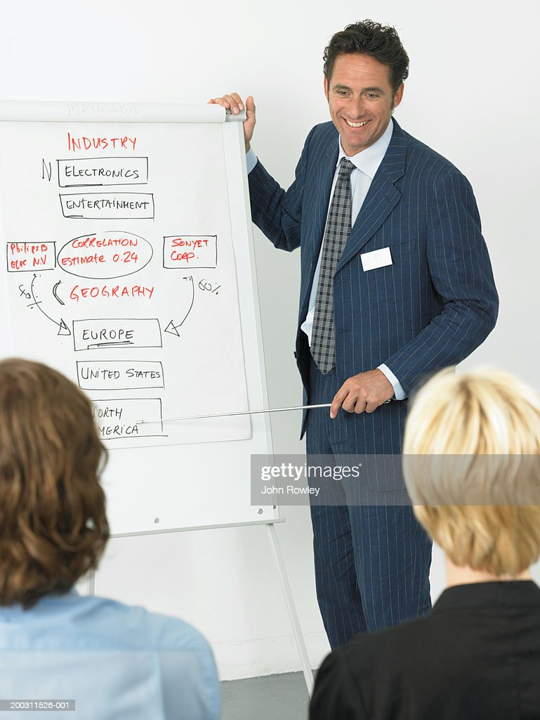 Businessman giving presentation, smiling, colleagues in foreground : Stock Photo