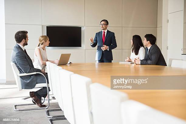 Businessman Giving Presentation To Colleagues At Conference Table