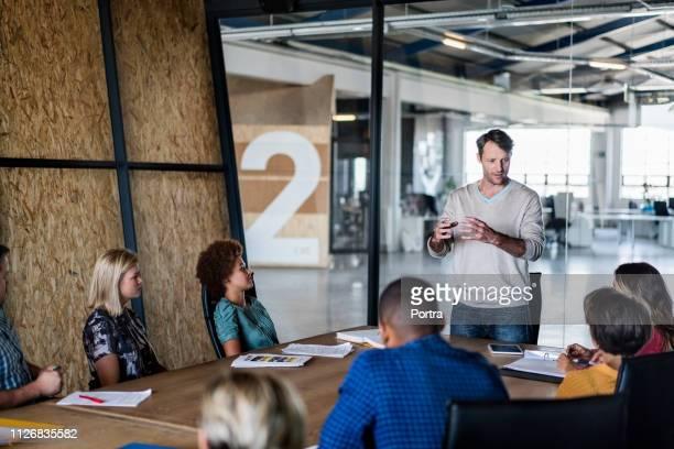 zakenman die presentatie geeft aan collega's - netjes informeel stockfoto's en -beelden