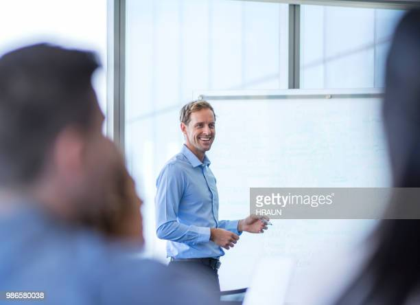 businessman giving presentation to colleagues - foco diferencial imagens e fotografias de stock