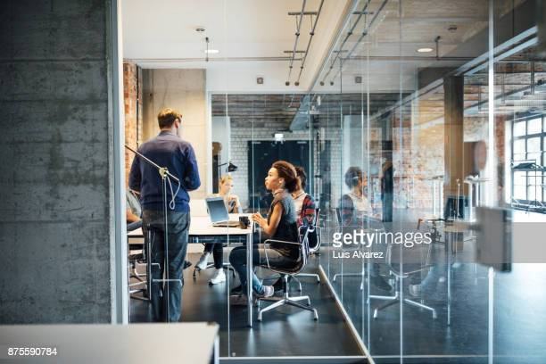 businessman giving presentation to colleagues seen through glass - büro stock-fotos und bilder
