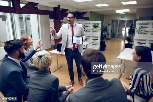 Businessman giving presentation to his team using digital tablet