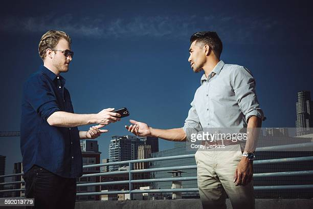 Businessman giving smartphone to man on roof terrace, Los Angeles, California, USA