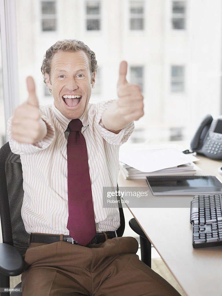 Businessman giving thumbs up : Stock Photo