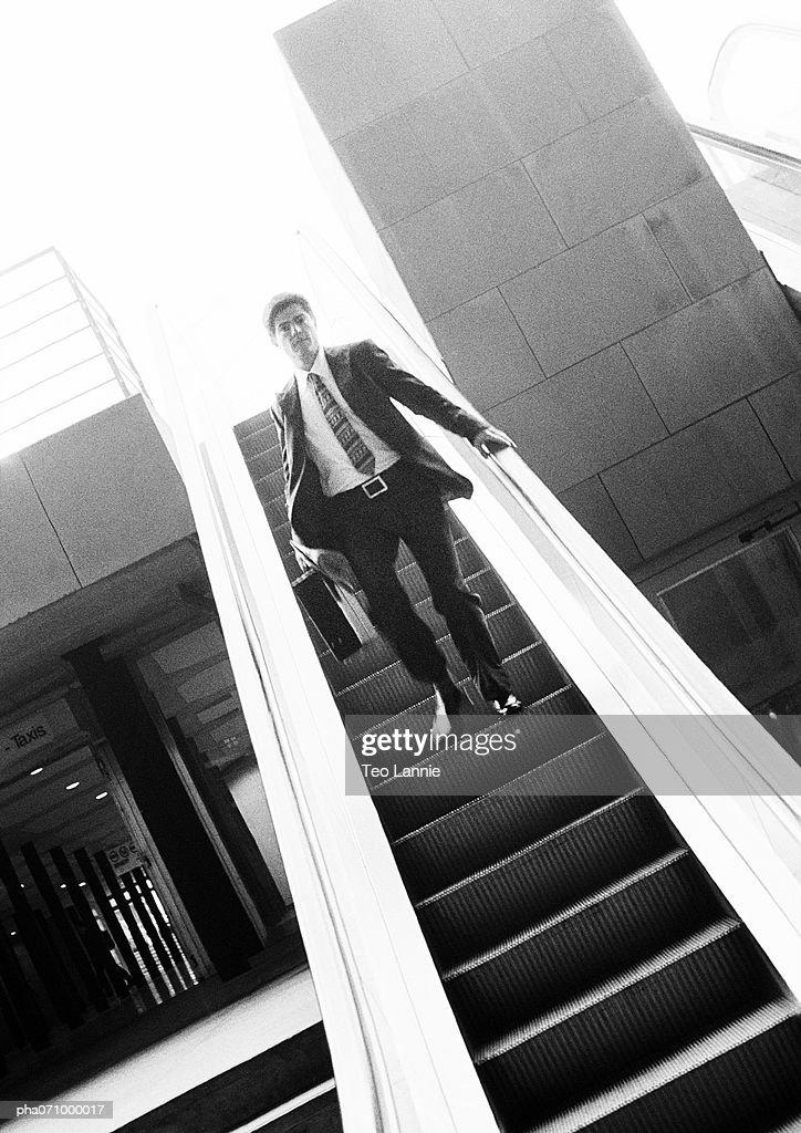 Businessman going down escalator, b&w. : Stockfoto