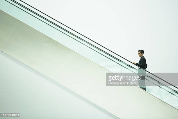 Businessman going up an escalator.