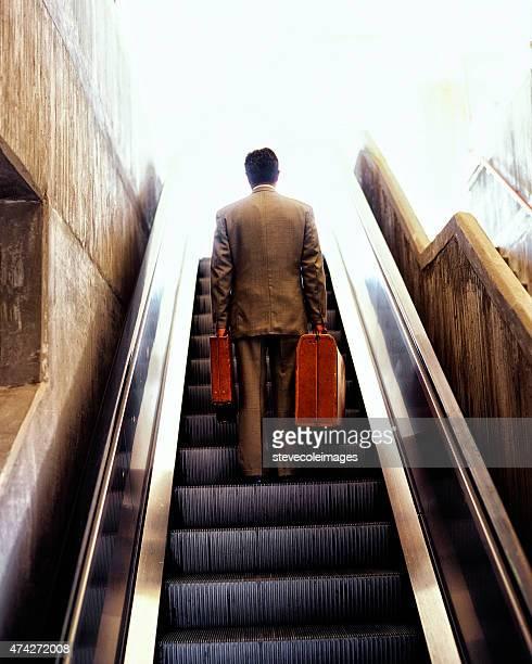 Uomo d'affari andando su scala mobile con i bagagli.