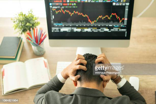businessman grabs the head concept with business chart on scoreboard - crash photos stock photos and pictures