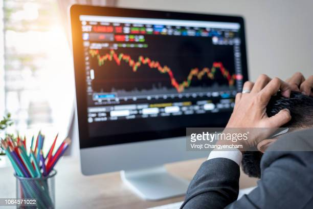 businessman grabs the head with stock market chart down