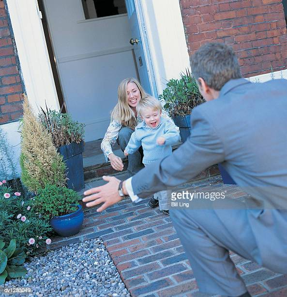 Businessman Greeting a Mother and Son on a Path in His Front Yard