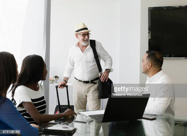 businessman greeting colleagues in office meeting - road warrior stock photos and pictures