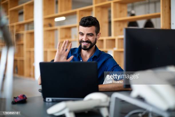 businessman greeting during a video call at his desk - opening event stock pictures, royalty-free photos & images