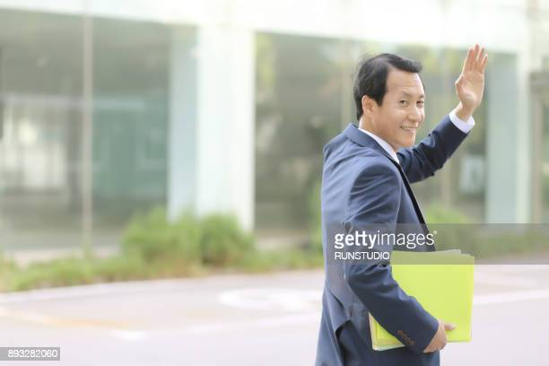 businessman greeting someone outside office - waving gesture stock photos and pictures