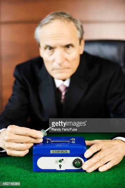 Businessman Guarding Cash Box