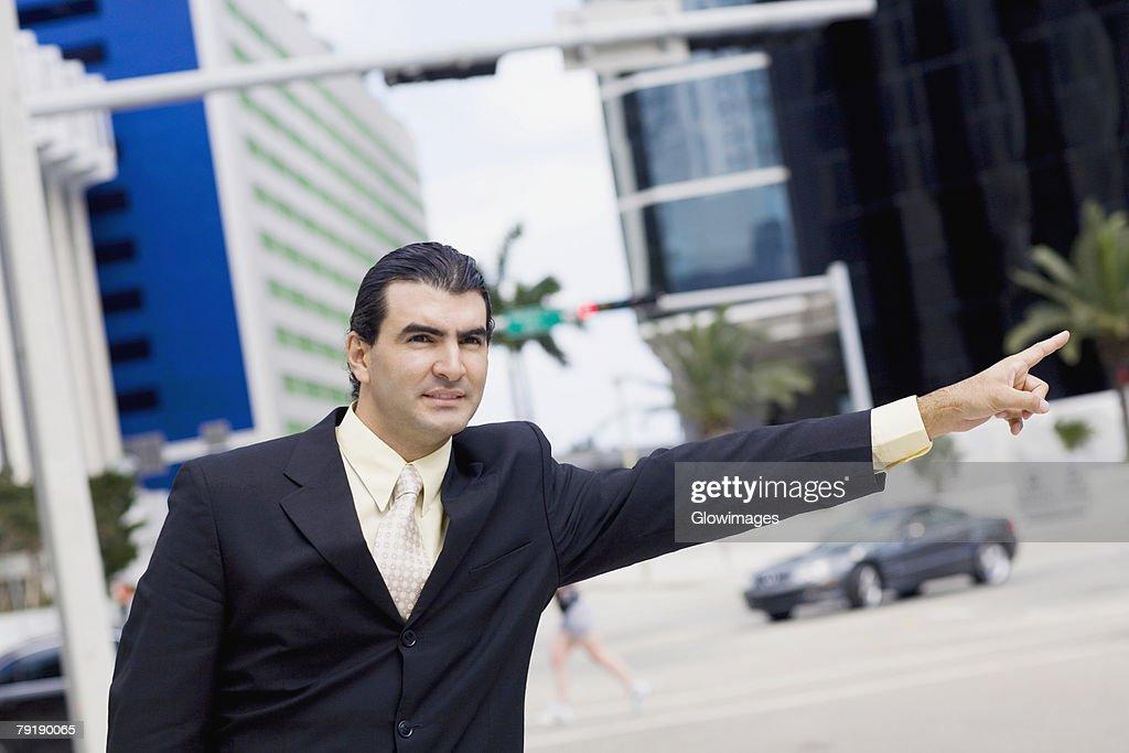Businessman hailing a vehicle : Stock Photo