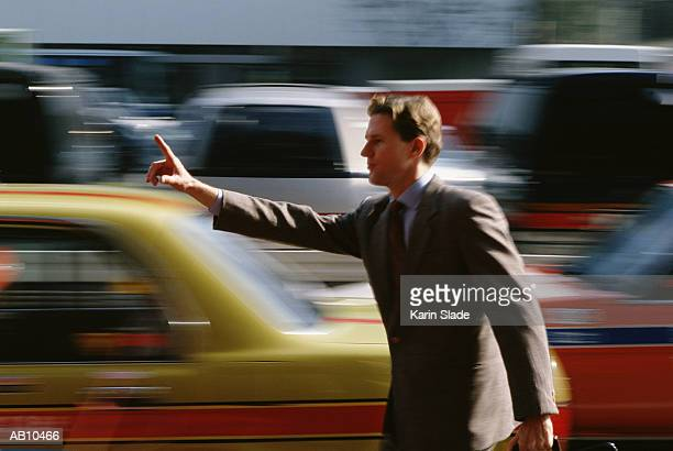Businessman hailing taxi in busy street