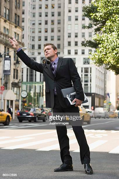 Businessman hailing taxi in city