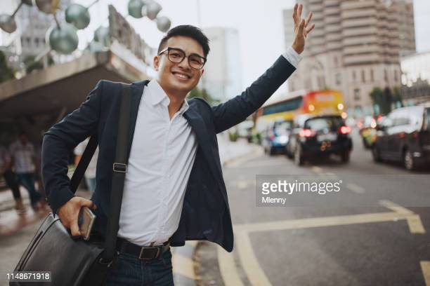 businessman hailing taxi kuala lumpur - waving gesture stock photos and pictures