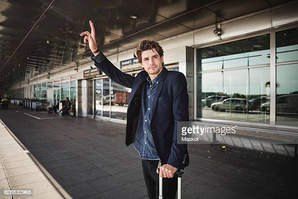 Businessman hailing taxi while standing outside airport