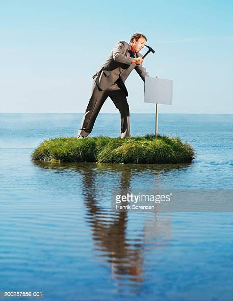 Businessman hammering sign post into ground on grass island