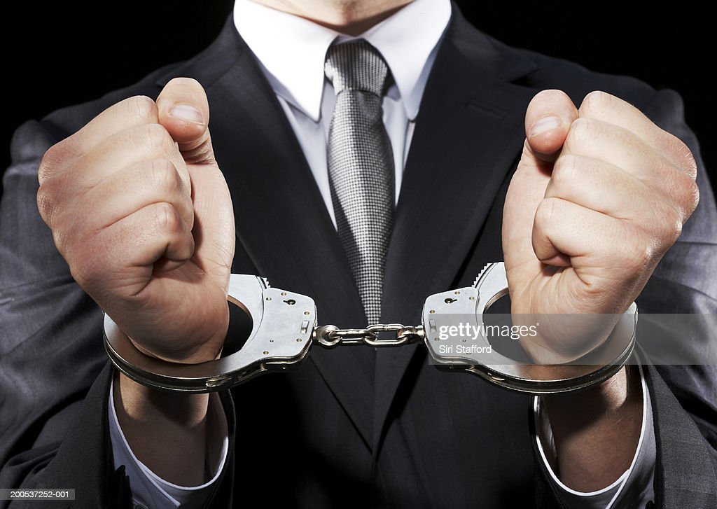 Businessman hand cuffed (mid section) : Stock Photo