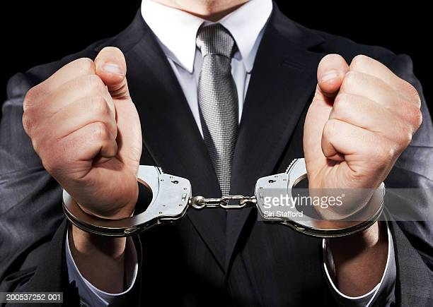 businessman hand cuffed (mid section) - handcuffs stock pictures, royalty-free photos & images