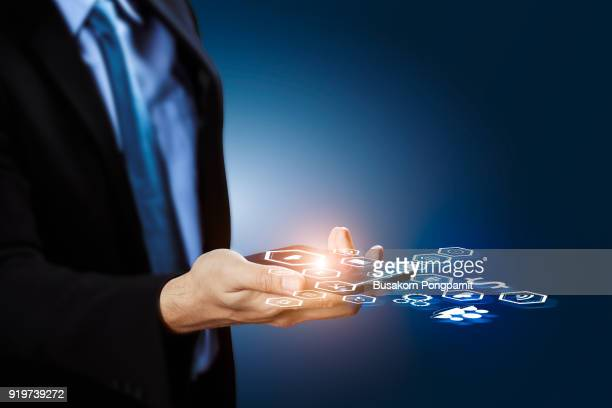 Businessman hand holding smartphone with icons with technology, internet and application concep