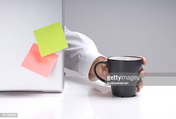 Businessman hand is reaching to hold a mug