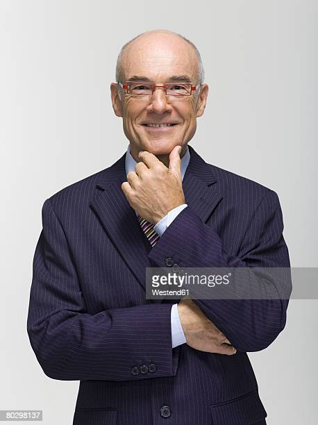 Businessman smiling, hand on chin, portrait, close-up