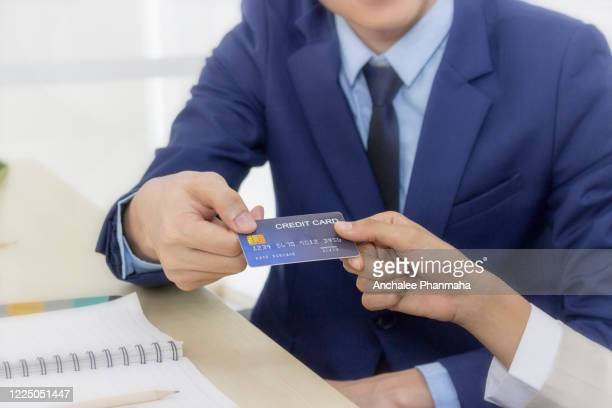 businessman hand sending credit card to the lady for online shopping pay - send stock pictures, royalty-free photos & images